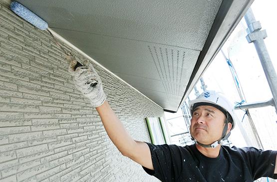 住宅の軒天を塗装する塗装職人