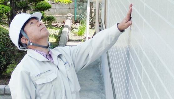 住宅の外壁を診断する一級建築士